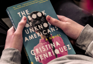 """Student holding the book, """"The Book of Unknown Americans"""""""